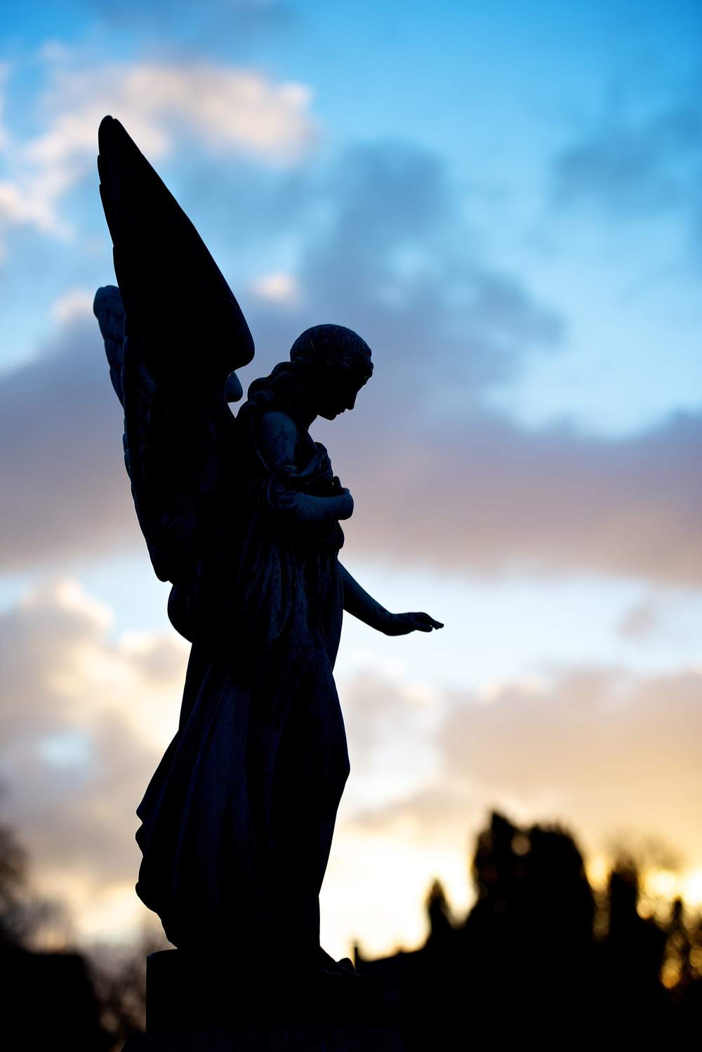 The statue of an angel at sunset with the sky lit up, and the statue in shadow.